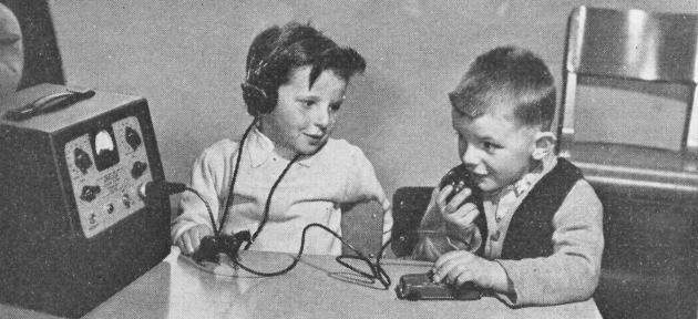 Two children learning to use hearing aid equipment